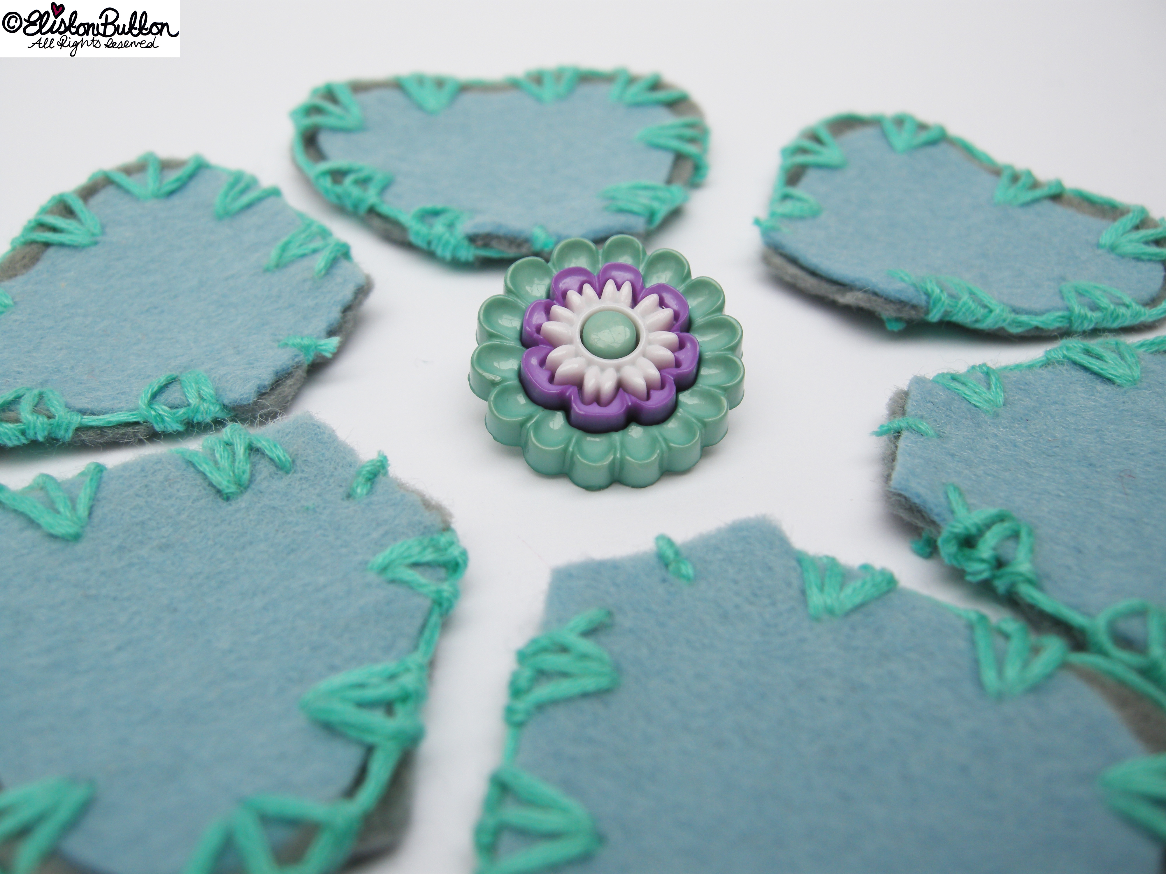 Pastel Blue and Grey Felt Petal Shapes Embroidered with Turquoise Embroidery Thread with Flower Button Centrepiece - 27 Before 27 – Aquamarine at www.elistonbutton.com - Eliston Button - That Crafty Kid – Art, Design, Craft & Adventure.