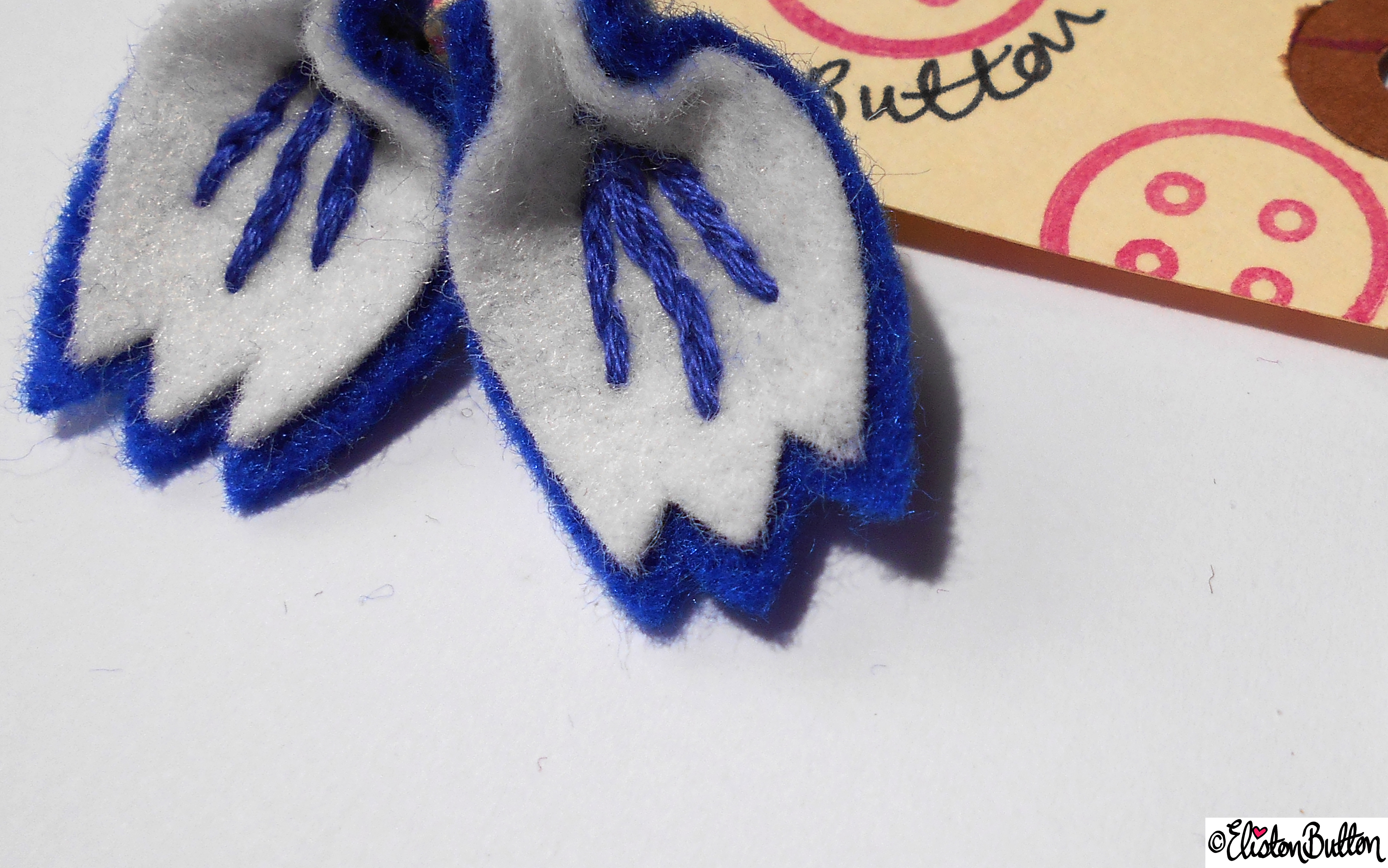 Blue and White Embroidered Felt Petal Earrings and Eliston Button Tag Close Up - Create 28 - No.2 - Embroidered Felt Petal Earrings at www.elistonbutton.com - Eliston Button - That Crafty Kid – Art, Design, Craft & Adventure.