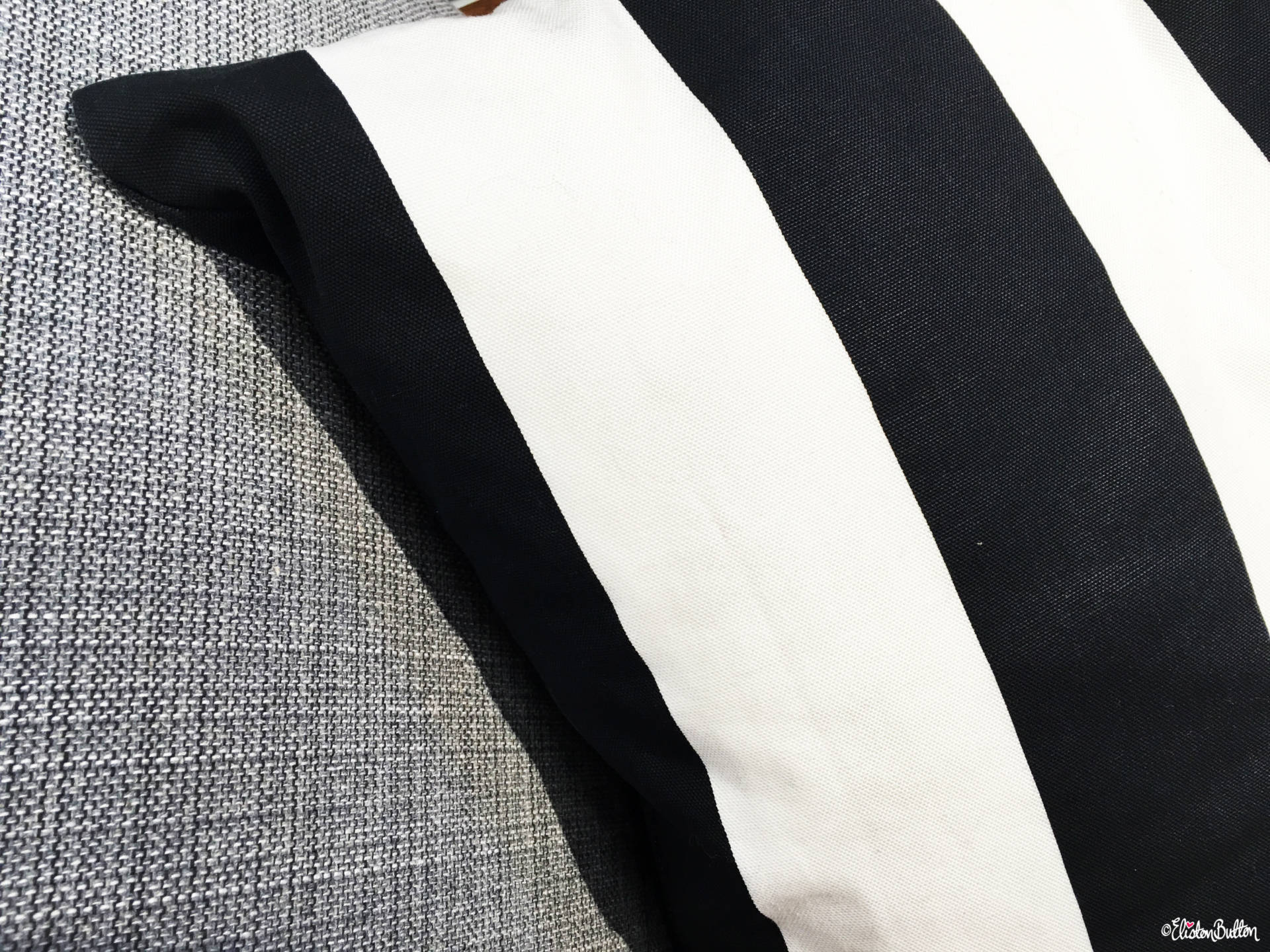 Black And White Bold Striped Cushion And Woven Grey Sofa