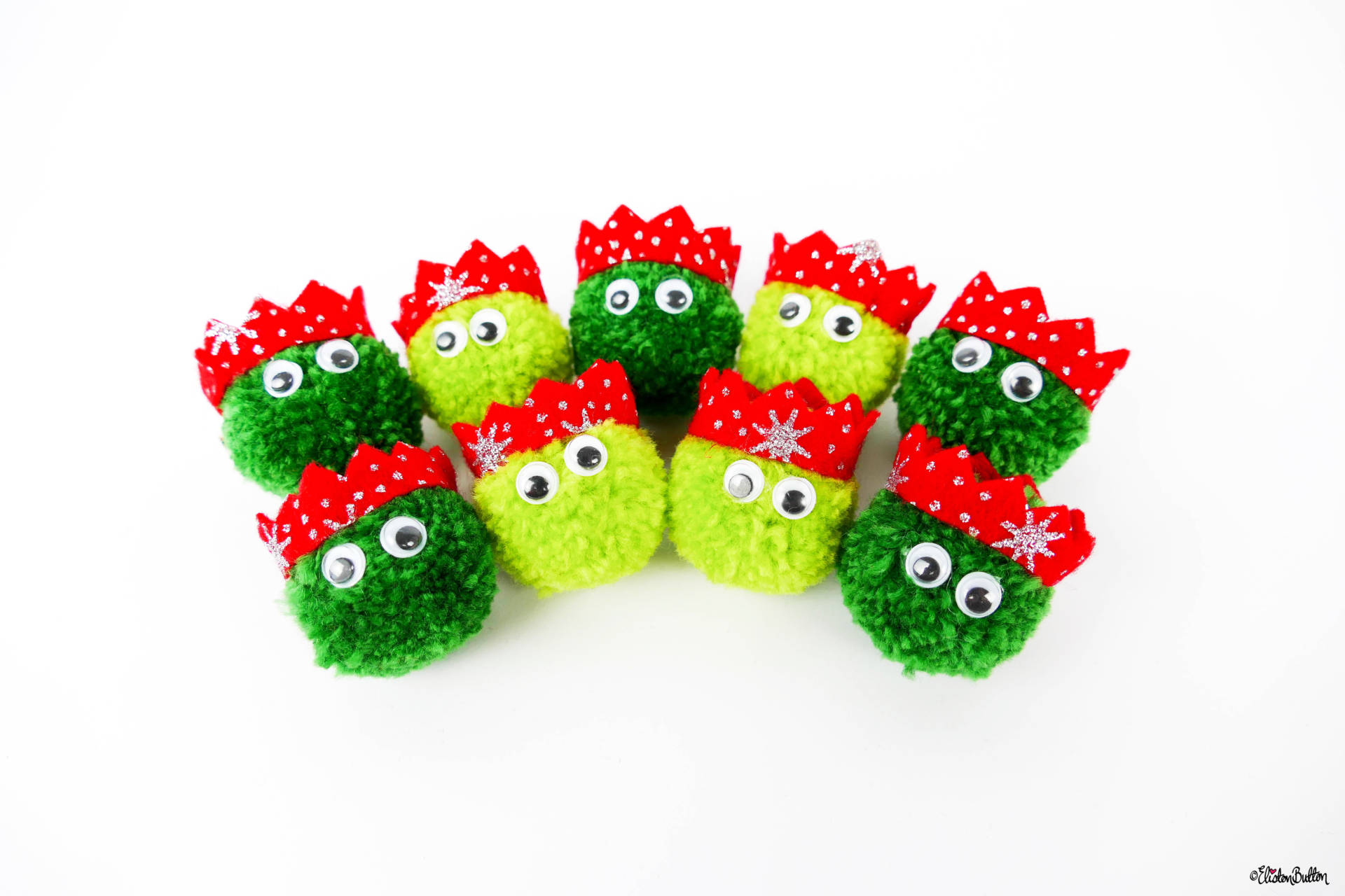 A Flock of Dark and Light Green Christmas Sprout Pom Pom Brooches with Red Glitter Party Hats by Eliston Button - Christmas Sprout Pom Pom Brooches! at www.elistonbutton.com - Eliston Button - That Crafty Kid – Art, Design, Craft & Adventure.