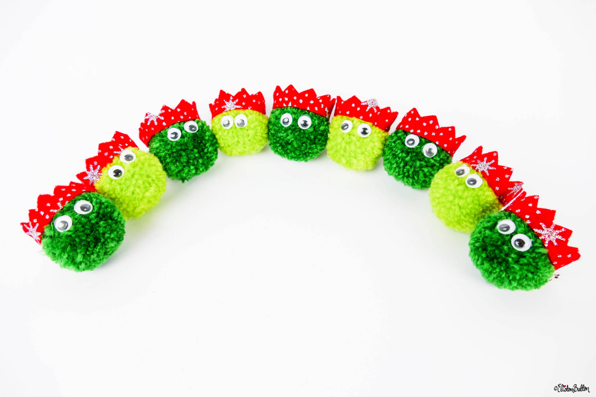 An Arch of Dark and Light Green Christmas Sprout Pom Pom Brooches with Red Glitter Party Hats by Eliston Button - Christmas Sprout Pom Pom Brooches! at www.elistonbutton.com - Eliston Button - That Crafty Kid – Art, Design, Craft & Adventure.