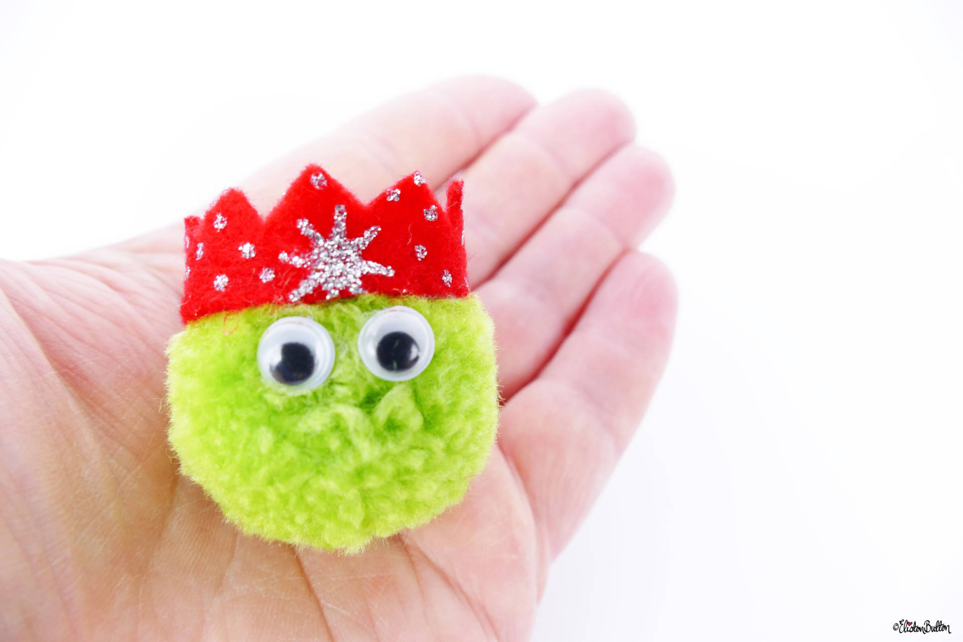 Light Green Christmas Sprout Pom Pom Brooch by Eliston Button in Hand for Size - Christmas Sprout Pom Pom Brooches! at www.elistonbutton.com - Eliston Button - That Crafty Kid – Art, Design, Craft & Adventure.